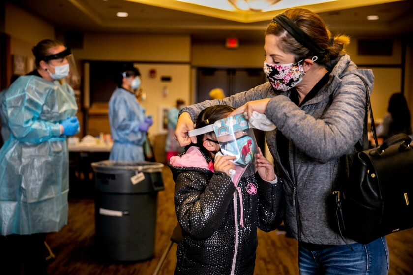 Brenda Alva helps her daughter Natalia Alva, 8, put her face shield back on after taking a COVID-19 test.