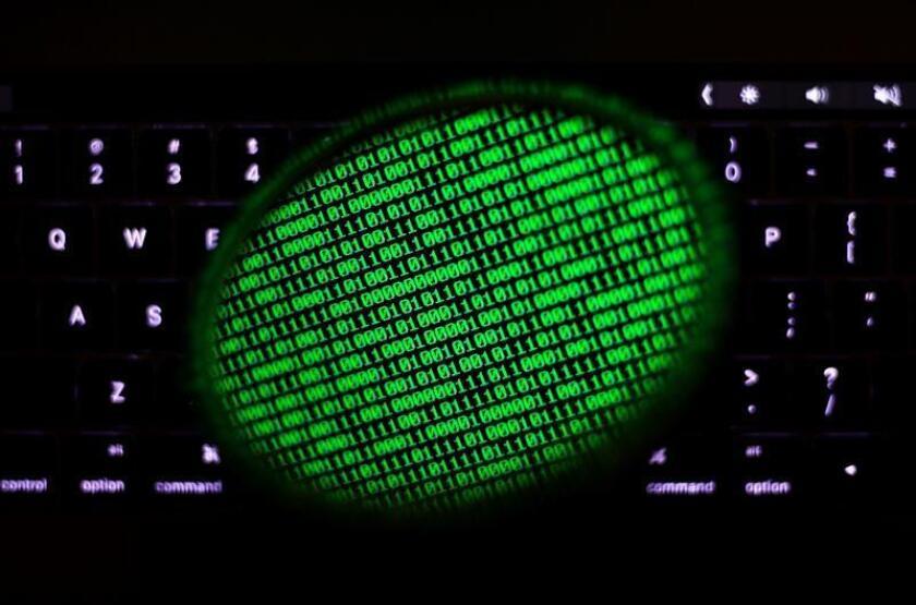 Fotografía de archivo fechada el 28 de junio de 2017 que muestra un espejo que refleja un código binario en una pantalla de ordenador, en Taipei (Taiwán). EFE/Archivo