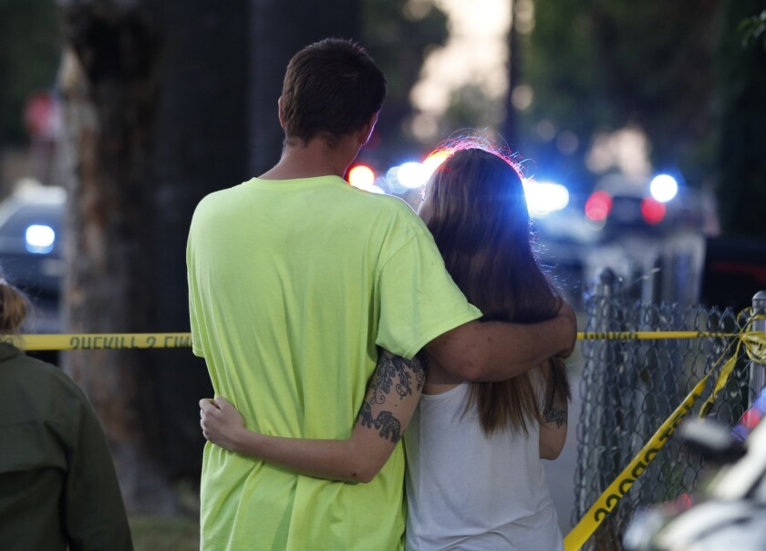 A man and woman watch as law enforcement officers surround a home where a gunman has taken refuge af