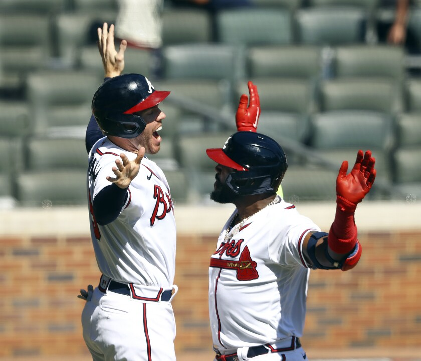 Atlanta Braves' Marcell Ozuna, right, and Freddie Freeman celebrate after Ozuna hit a two-run home run in the eighth inning against the Cincinnati Reds in Game 2 of a National League wild-card baseball series, Thursday, Oct. 1, 2020, in Atlanta. (Curtis Compton/Atlanta Journal-Constitution via AP)