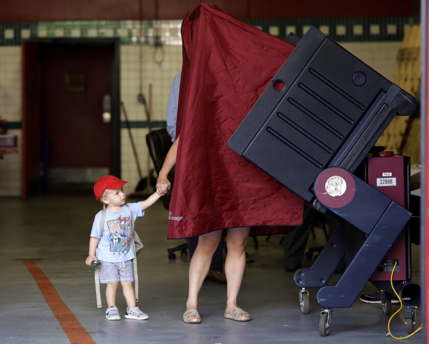 James Percella, 2, holds his mother's hand as she steps into a voting booth in Hoboken, N.J., on June 7.