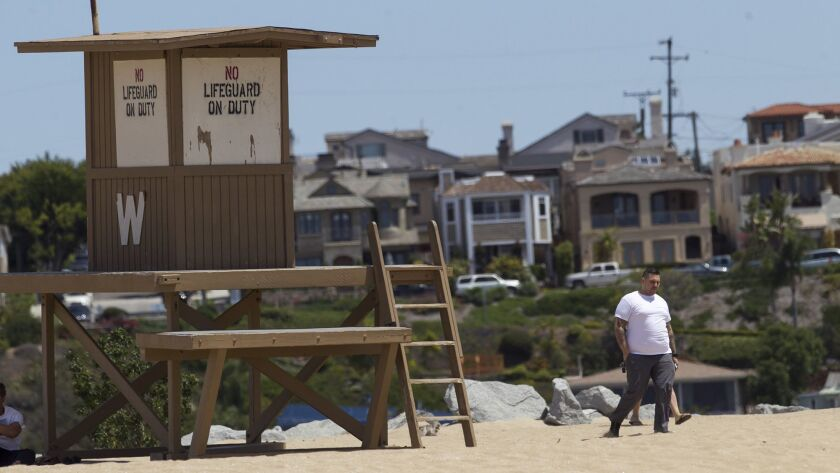 NEWPORT BEACH, May 1, 2014 - Spectators walk past an unmanned lifeguard tower while body surfers cat