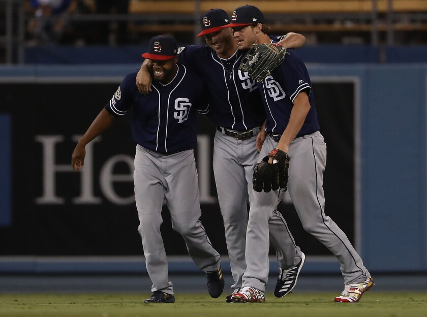 Manuel Margot, left, Hunter Renfroe, center, and Wil Myers celebrate as they walk in from the outfield at the end of Saturay night's vitory over the Dodgers.