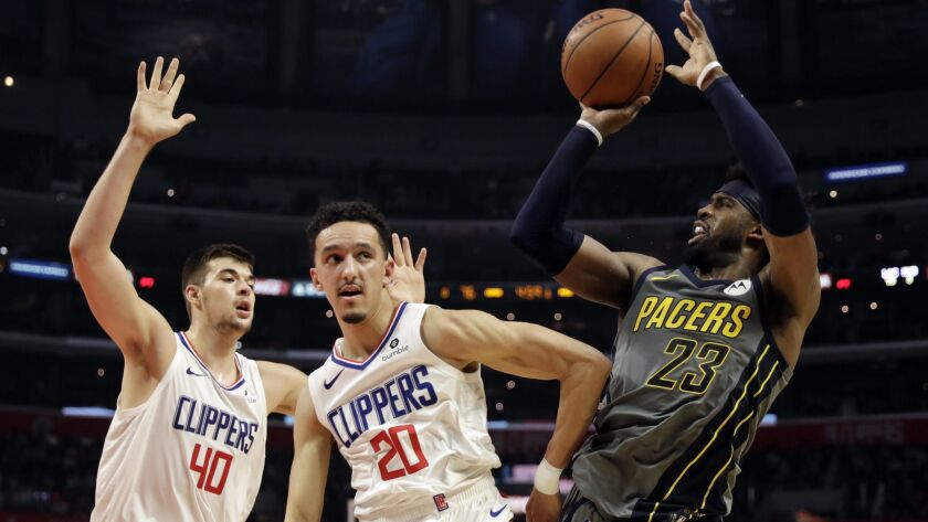 Clippers guard Landry Shamet (20) and center Ivica Zubac (40) force Pacers guard Wesley Matthews into a difficult shot during their game Tuesday.