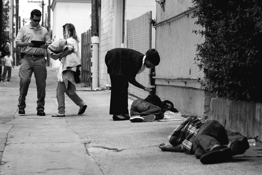RAP paramedic Shawn Percival talks to a homeless woman as Lucky Michael, a homeless outreach coordinator for the Downtown San Diego Partnership, talks to  Thomas Pappas, 63, after they found the woman, Pappas, and Robert Stevens, 61, foreground, sleeping in an alley in Hillcrest