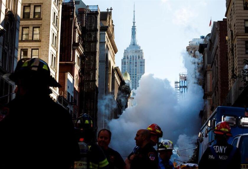 Varios bomberos trabajan en el lugar donde una tubería de vapor explotó en Manhattan, en la Quinta Avenida con la calle 21 Este, causando la evacuación de once edificios y cortes de tráfico desde la calle 19 hasta la 23 y entre La Sexta y Broadway, en Nueva York, EEUU. EFE/Archivo