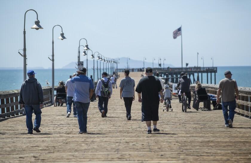 People visit the Ventura Pier on Monday.