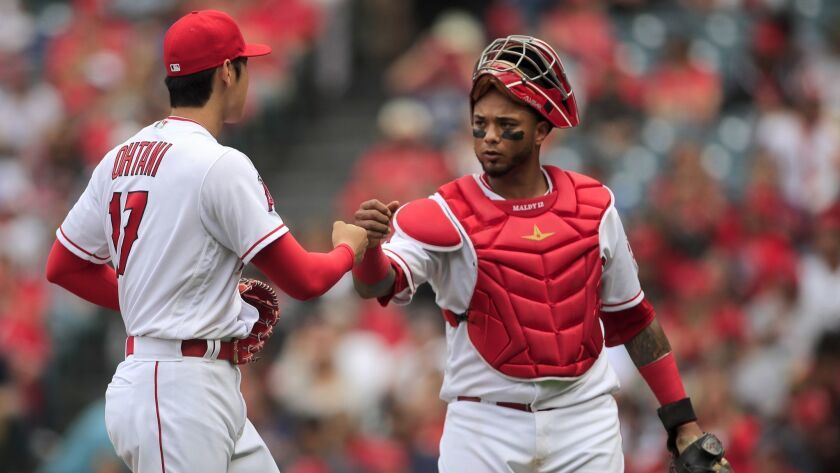 ANAHEIM, CALIF. -- SUNDAY, MAY 20, 2018: Angels starting pitcher Shohei Ohtani fist-bumps with catch