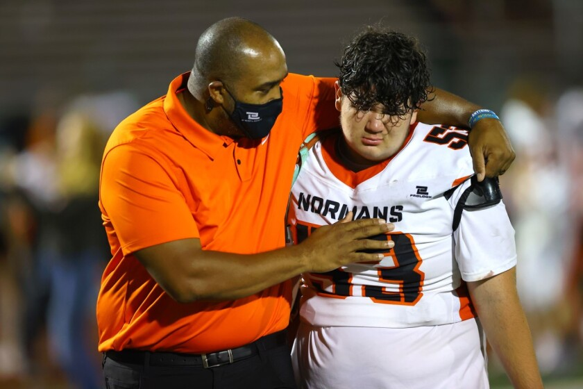 Beverly Hills coach Marquis Bowling consoles a freshman after a game.