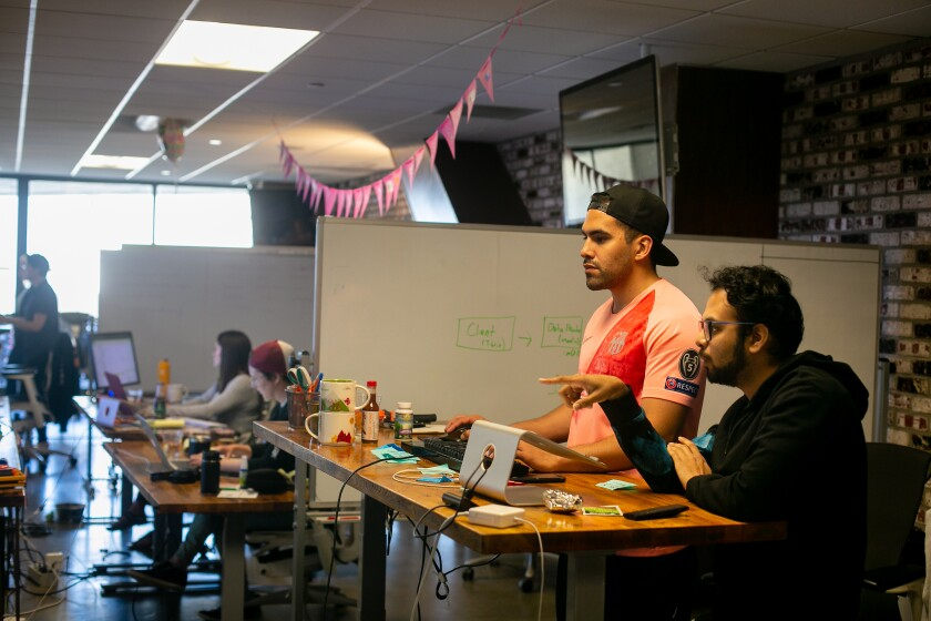 Software engineers Adrian Eufracio and Digant Jagtap work together at Zeeto, an internet marketing company in San Diego.