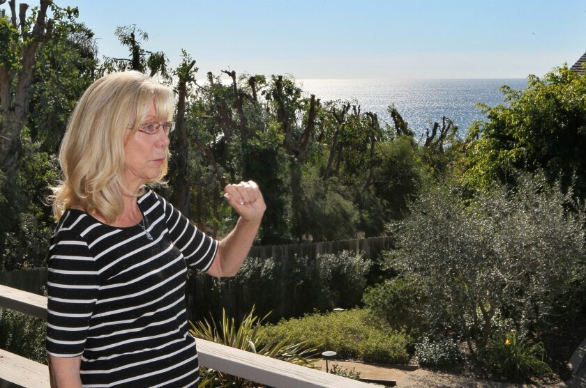 Judy Hunt stands on her balcony at the Del Mar Woods condo development speaking of her and neighbors frustration at the eucalyptus trees shown in the distance blocking their ocean views.