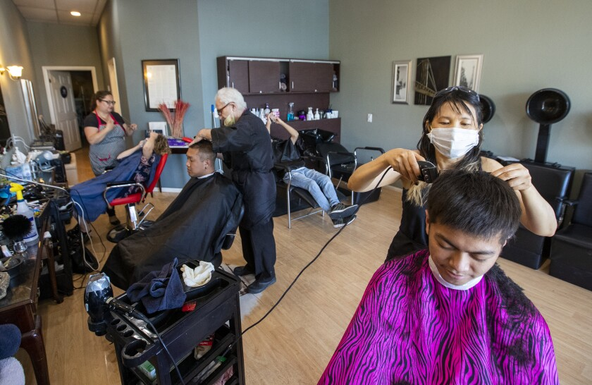 At the Hair Event in Fullerton, Kristy Rana, far left, threads Maureen Harry's eyebrows, salon owner Zaharia Bala cuts Ahmad Bitar's hair, center, and Kylee Liu cuts Anthony Arevalo's hair on Tuesday.