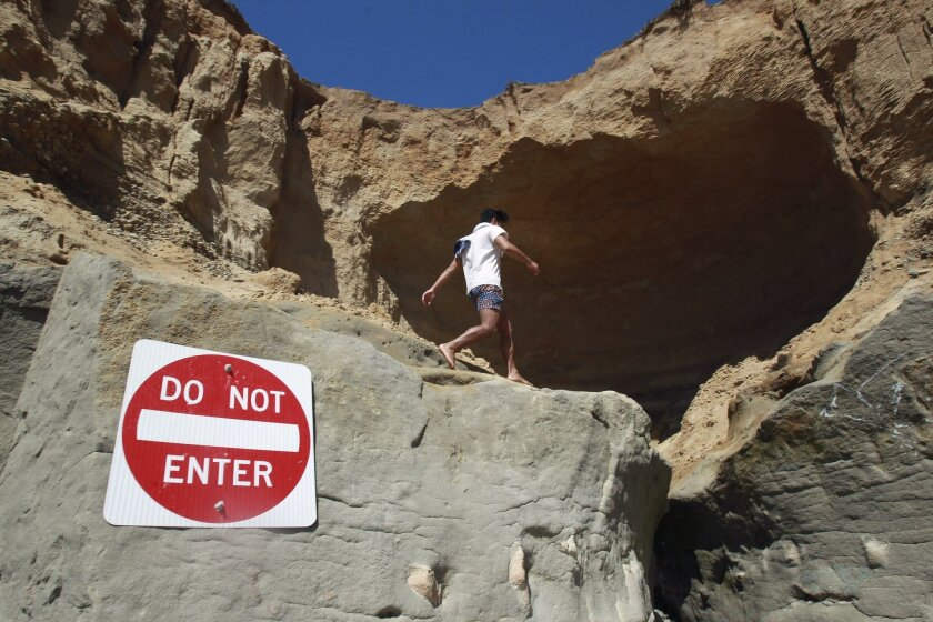 A man walks near a cave that has formed on a section of beach bluff that has eroded in Carlsbad.