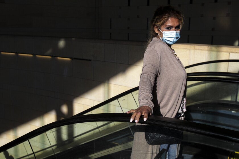 At Union Station in Los Angeles, a woman on an escalator wears a mask.