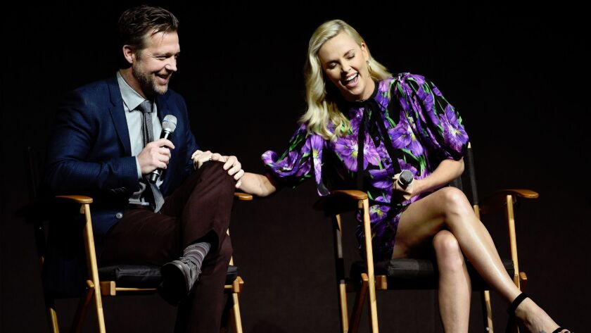 "Charlize Theron, right, star of ""Atomic Blonde,"" shares a laugh with the film's director David Leitc"