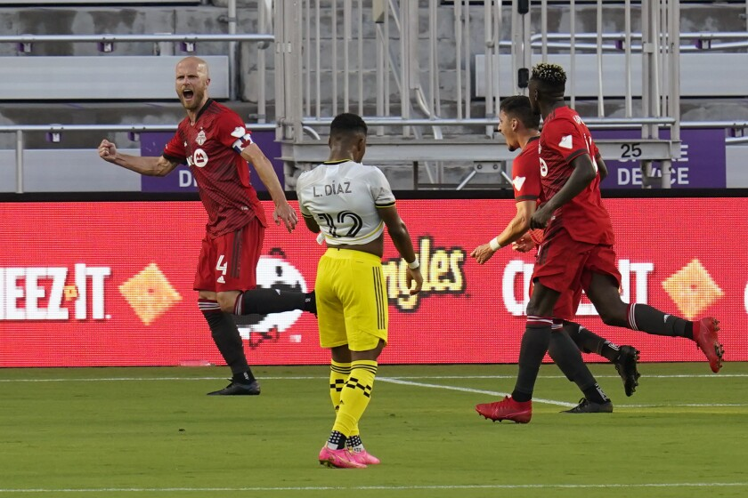 Toronto FC midfielder Michael Bradley (4) celebrates with teammates after scoring a goal against the Columbus Crew as Columbus Crew midfielder Luis Diaz (12) walks away during the first half of an MLS soccer match, Wednesday, May 12, 2021, in Orlando, Fla. (AP Photo/John Raoux)