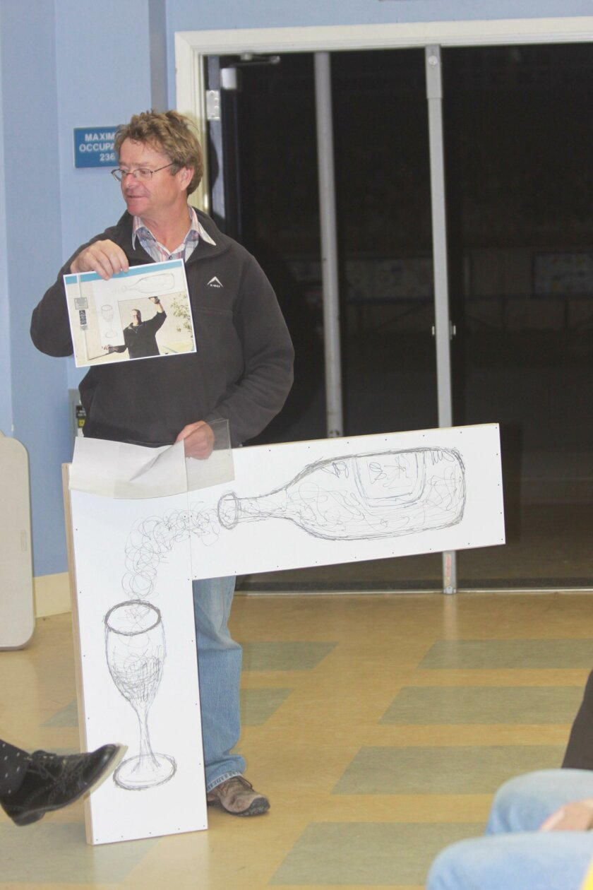 Lowell Jooste shows a planned decoration for his wine shop on La Jolla Boulevard.