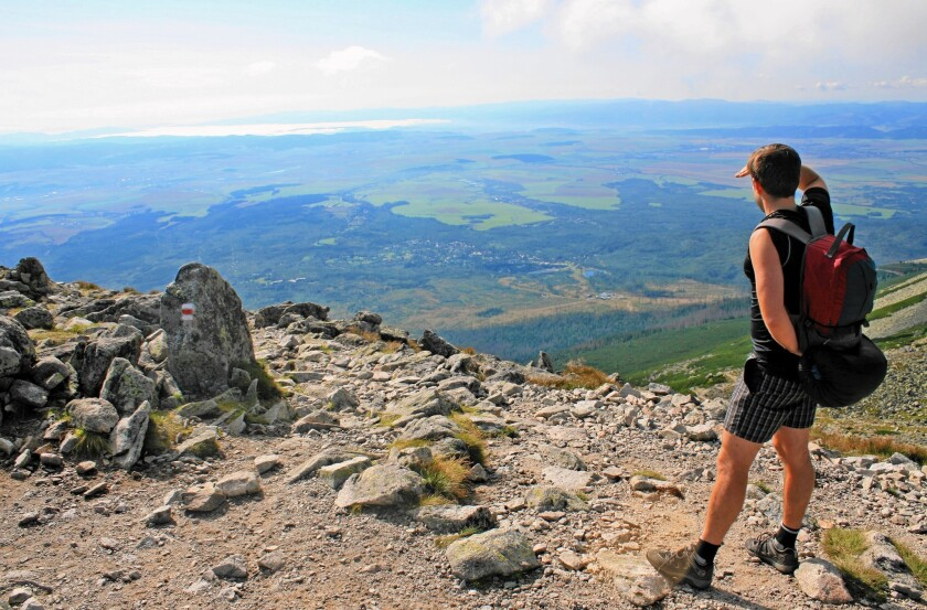 High Tatras views enchant hikers in Slovakia; well-marked trails guide them; cozy huts welcome them.