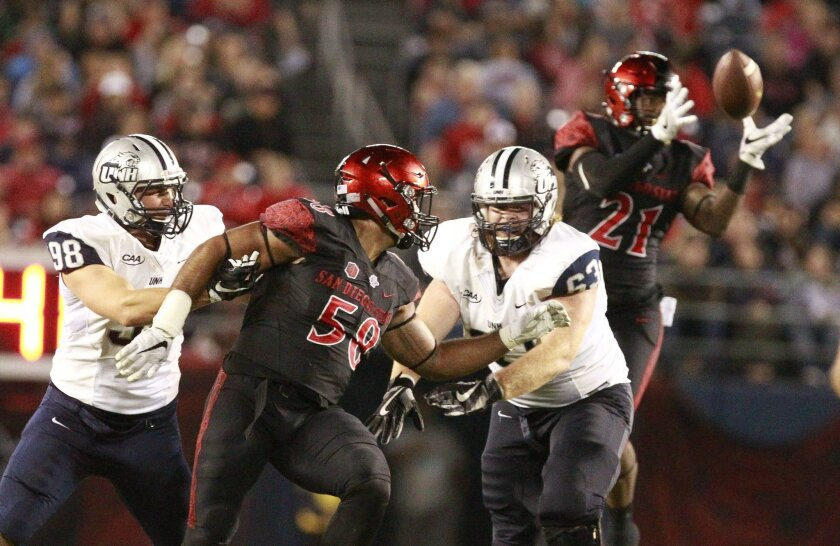New Hampshire's John DiCaro, left, and Nick Velte grab the Aztecs' Alex Barrett, center, as Na'im McGee, right, grabs an interception in the fourth quarter.