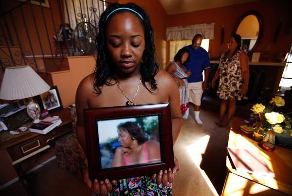 Khristina Henry holds a photo of her mother, Pamela Lark. Lark adamantly wanted her daughter to testify in the robbery trial of a former high school football star accused of robbing Henry and a friend at gunpoint.