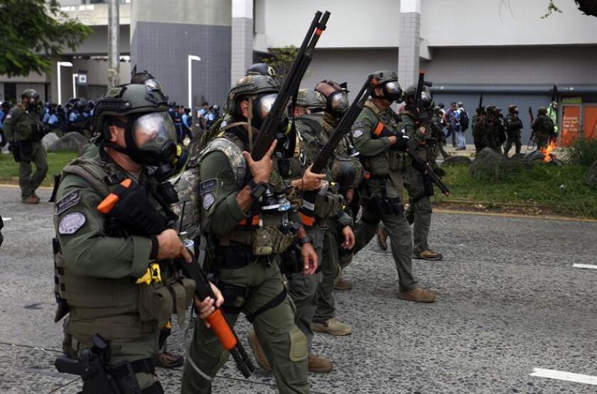 Unos policías antidisturbios caminan por una calle durante una manifestación de polícias retirados en Puerto Rico. EFE/Archivo