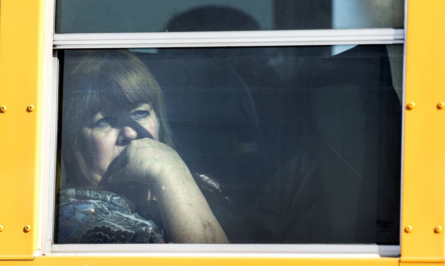 A woman looks out the window as she and others leave in school buses as they evacuate a site in San Bernardino, Calif., Wednesday, Dec. 2, 2015. Multiple attackers opened fire on a banquet at a social services center for the disabled in San Bernardino on Wednesday, killing multiple people and sendi