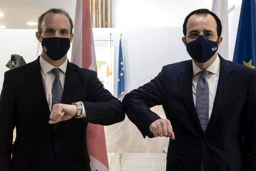 Cypriot Foreign Minister Nicos Christodoulides, right, and Britain's Secretary of State for Foreign Affairs, Dominic Raab, clad due before their meeting at the foreign house in capital Nicosia, Cyprus, Thursday, Feb. 4, 2021. Raab is in Cyprus for one day of talks (Iakovos Hatzistavrou Pool via AP)