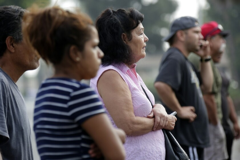 Neighbors watch as Los Angeles County sheriff's detectives investigate in Pico Rivera on Saturday after a gun battle between deputies and a wanted parolee left an innocent bystander dead.