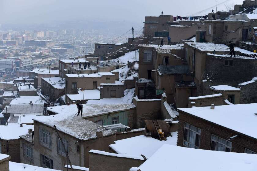 Afghan residents remove snow from the roofs of houses overlooking Kabul on Jan. 25. In the northeast of the country, at least 100 people have been killed in avalanches following severe snowfall.