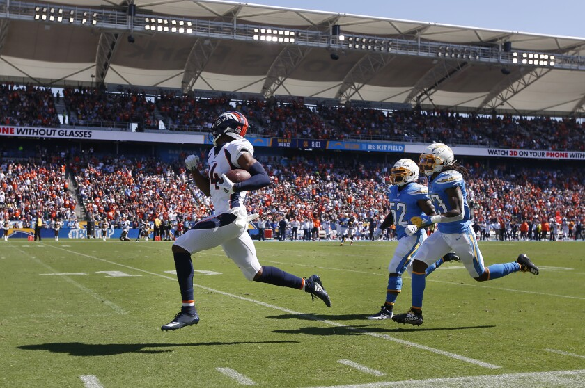 Denver's Courtland Sutton runs in for a 70-yard touchdown in front of Chargers' Denzel Perryman (52) and Rayshawn Jenkins in the first quarter Sunday in Carson.