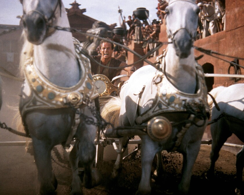 "Charlton Heston in costume and riding a horsedrawn chariot in a publicity still for the 1959 film ""Ben-Hur."""