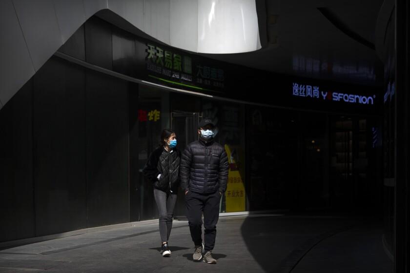 Dos personas con mascariilas pasan por un complejo de edificios en Beijing, el 20 de marzo de 2020. (AP Foto/Mark Schiefelbein)