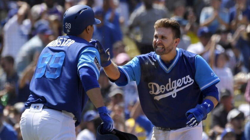 The Dodgers' Hyun-Jin Ryu, left, and Brian Dozier celebrate after they scored on a double by Justin Turner during the fifth inning against the San Diego Padres on Sunday.