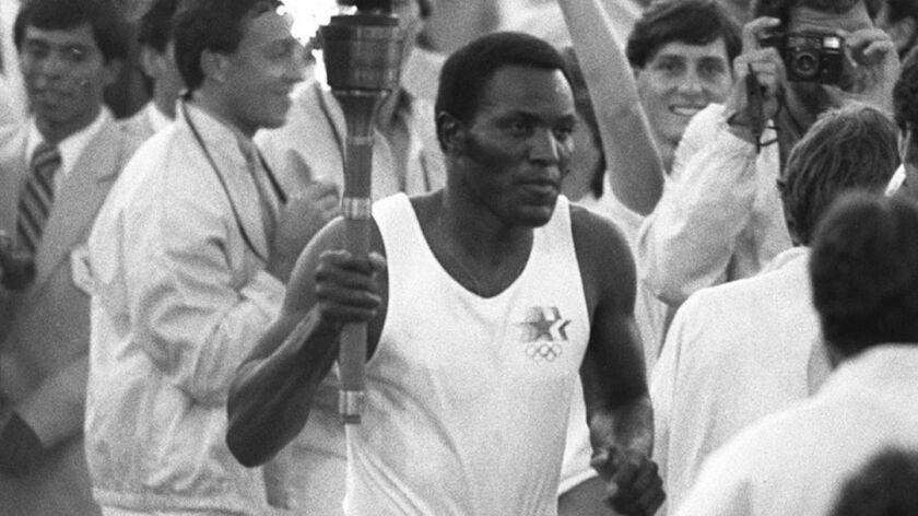 Rafer Johnson runs around the track at the Coliseum before lighting the Olympic flame in 1984.