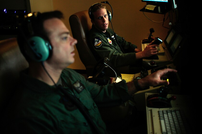 """Sgt. James Jochum, left, and Capt. Sam Nelson at work at Creech Air Force Base in Nevada. """"Every single day this base is at war,"""" said Col. James R. Cluff, the commander of Creech. """"These kids are not playing video games out of their mothers' basements."""""""