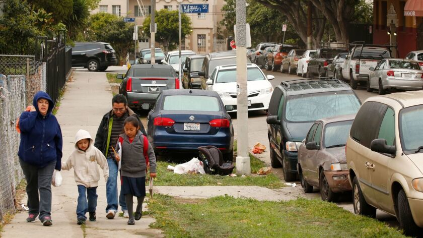 The Hernandez family walks along Miramar Street in Westlake, one neighborhood where a growing number of residents are parking their cars on the strip of land between the sidewalk and the curb.
