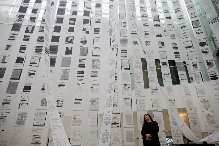 """In this July 13, 2016 photo, Chilean artist Voluspa Jarpa poses next to her installation, one day before the inauguration of her exhibit titled, """"En nuestra pequeña región de por acá,"""" or """"In Our Little Region Over Here,"""" at the MALBA museum in Buenos Aires, Argentina. Jarpa has turned declassified CIA documents into an exhibit focused on the thousands killed or forcibly """"disappeared"""" during one of Latin America's darkest periods. The show includes videos, audios and paintings. (AP Photo/Natacha Pisarenko)"""