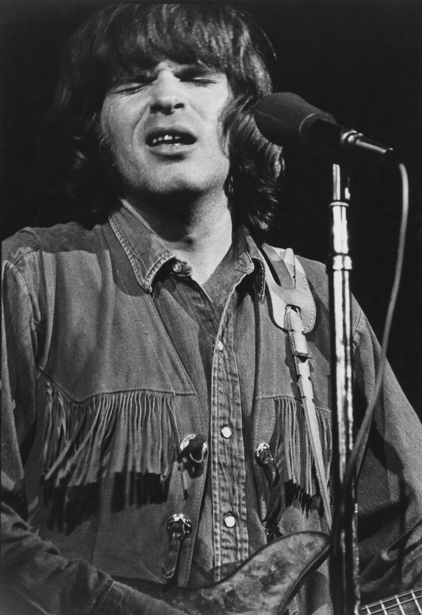 A closeup of young John Fogerty playing guitar and singing into a microphone.