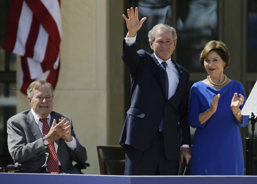 En esta imagen de archivo, tomada el 25 de abril de 2013, el expresidente de Estados Unidos George H.W. Bush (izquierda) aplaude a su hijo, el también expresidente George W. Bush, al lado de su esposa Laura, tras un discurso en el George W. Bush Presidential Center de Dallas. Bush padre critica por primera vez en público a miembros clave en el gobierno de su hijo en una nueva autobiografía.