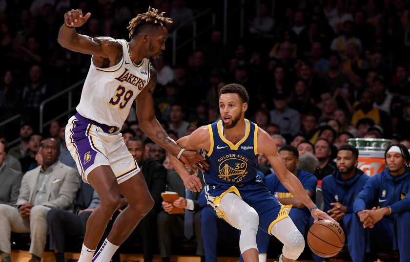 Golden State Warriors point guard Stephen Curry tries to drive around Lakers center Dwight Howard.