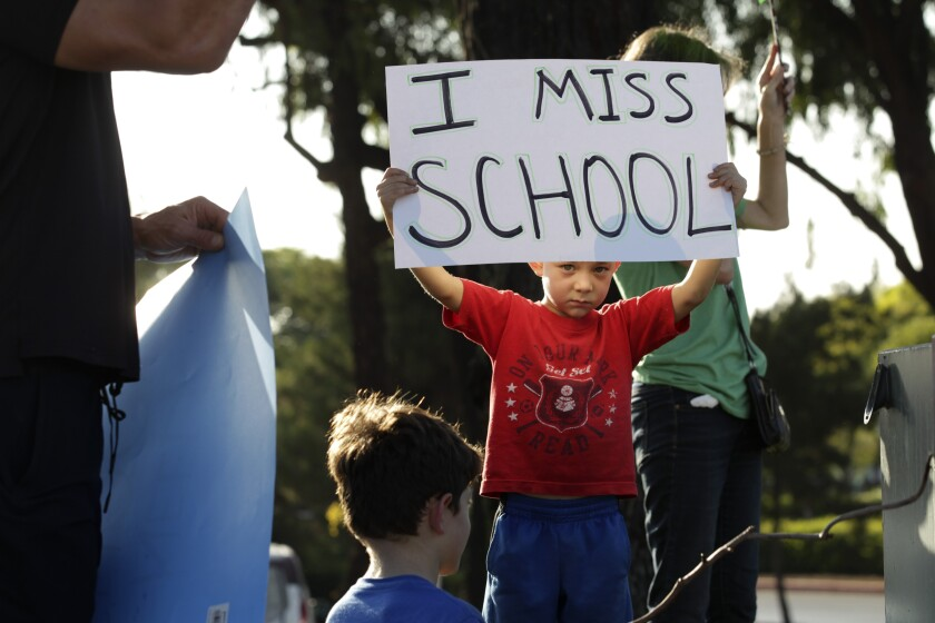 Jaycee Di Donato, 5, displays a sign urging officials to open schools at a protest at Carlsbad School district headquarters