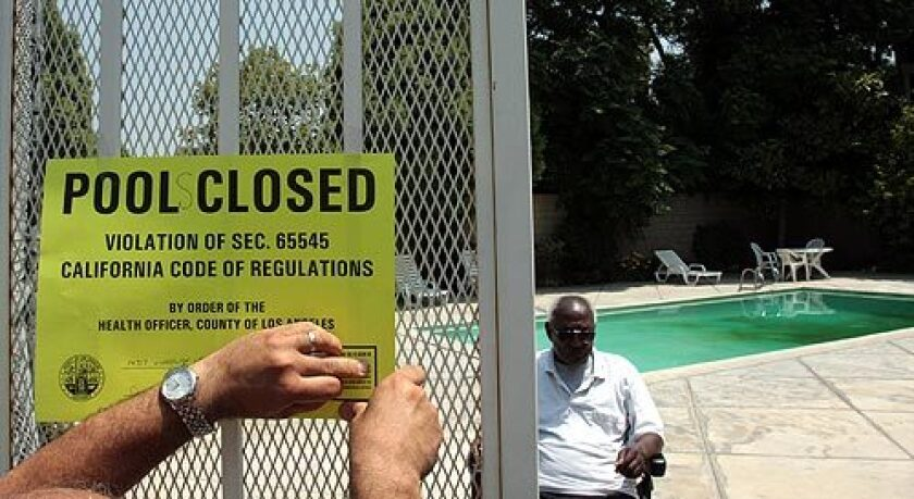 L.A. County inspector Sarkis Kharadjian closes an apartment complex's pool and spa in Panorama City as building manager Sylvester Norwood watches. More photos >>>