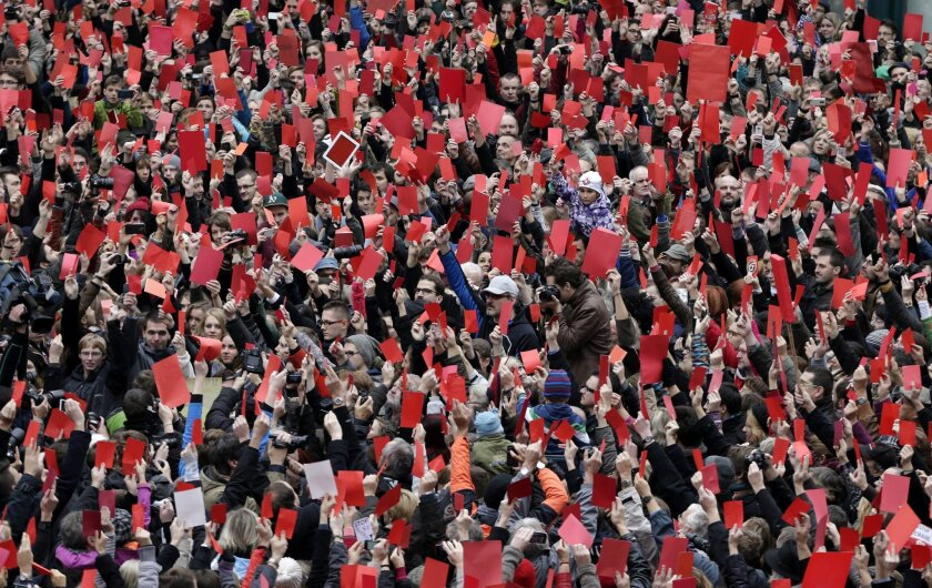Thousands of Czechs, using the 25th anniversary of the anti-communist Velvet Revolution, gather to call on the controversy-prone Czech President Milos Zeman to resign in Prague, Czech Republic, Monday, Nov. 17, 2014. The crowd gave Zeman a symbolic red card on Monday for demeaning the importance of