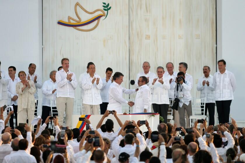 """El presidente de Colombia Juan Manuel Santos, en el centro a la izquierda, estrecha la mano del máximo comandante de las Fuerzas Armadas Revolucionarias de Colombia (FARC) Rodrigo Londoño, alias """"Timochenko"""", después de firmar un acuerdo de paz para poner fin a más de 50 años de conflicto en Cartagena, el lunes 26 de septiembre de 2016. (AP Foto/Fernando Vergara)"""