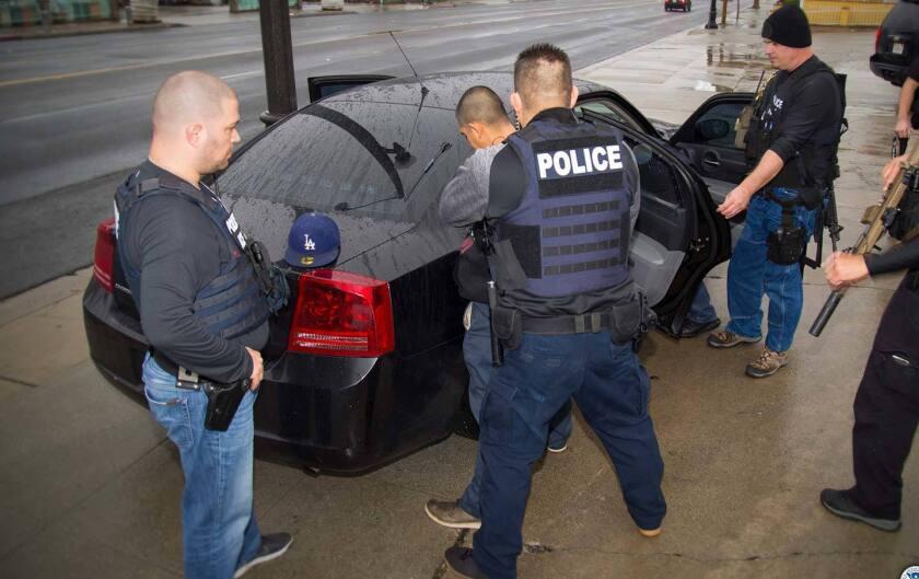 Agentes de ICE arrestan a un migrante sin documentos en una calle de Los Ángeles.
