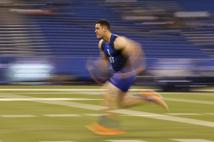 Navy long snapper Joe Cardona warms up before the 40-yard dash at the NFL football scouting combine