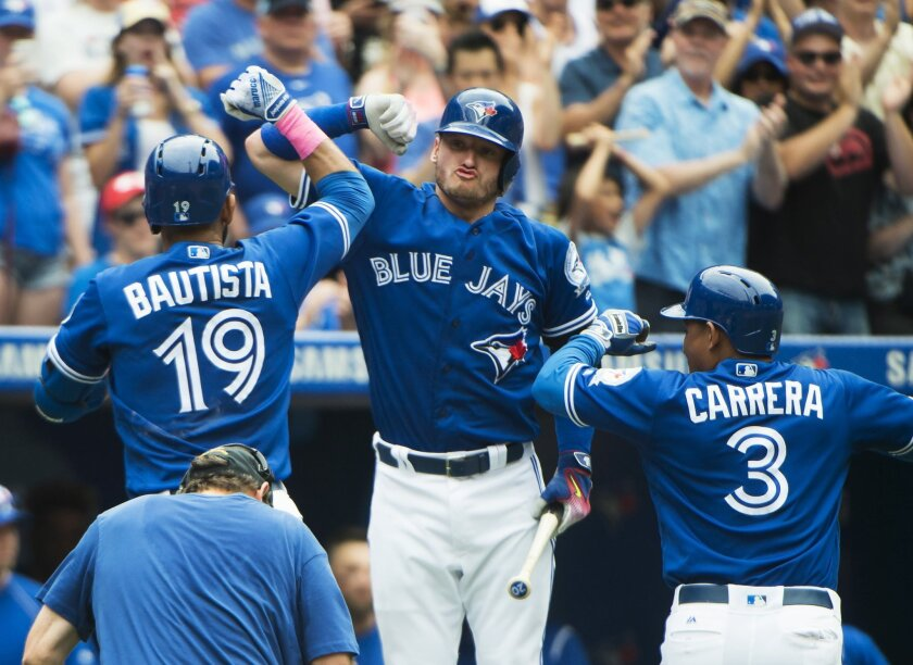 Toronto Blue Jays right fielder Jose Bautista (19) celebrates with teammates Josh Donaldson (20) and Ezequiel Carrera (3) after hitting a two-run home run against the Boston Red Sox during fifth-inning baseball game action in Toronto on Sunday, May 29, 2016. (Nathan Denette/The Canadian Press via A
