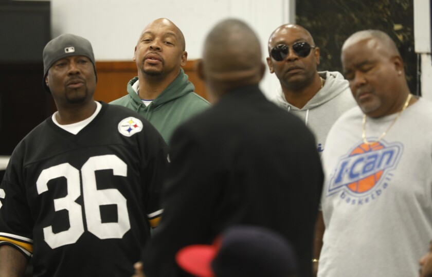 """Robinson """"G-Nutt"""" Lonnell, from left, Lamar """"Crocc"""" Robinson, in green hoodie, Kenyan """"Kenzo"""" Payne, sunglasses and others listen to Marvin Kincy, 69, of the Fruit Town Pirus,"""