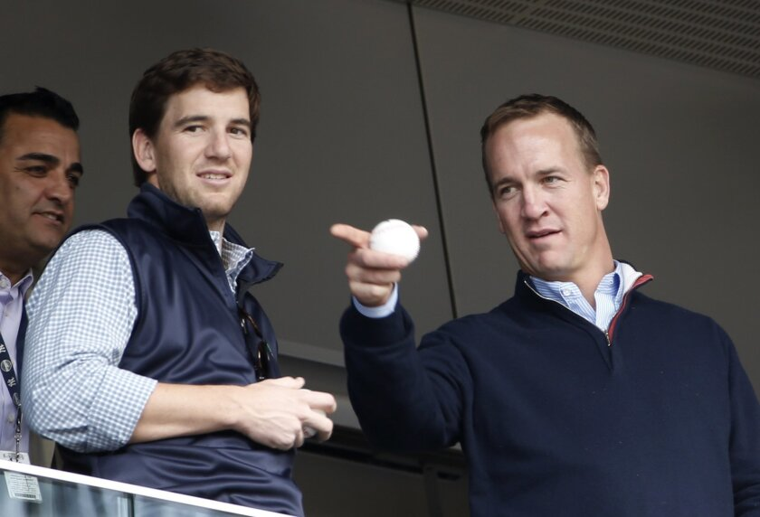 FILE - In this May 4, 2014, file photo, Denver Broncos quarterback Peyton Manning, right, points out something in the stadium to his brother, New York Giants quarterback Eli Manning, from New York Yankees' Derek Jeter's suite during a baseball game between the Yankees and the Tampa Bay Rays at Yank