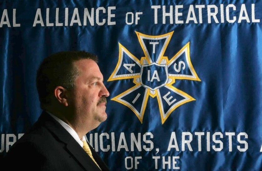 IATSE President Matthew Loeb stands in front of a union banner.